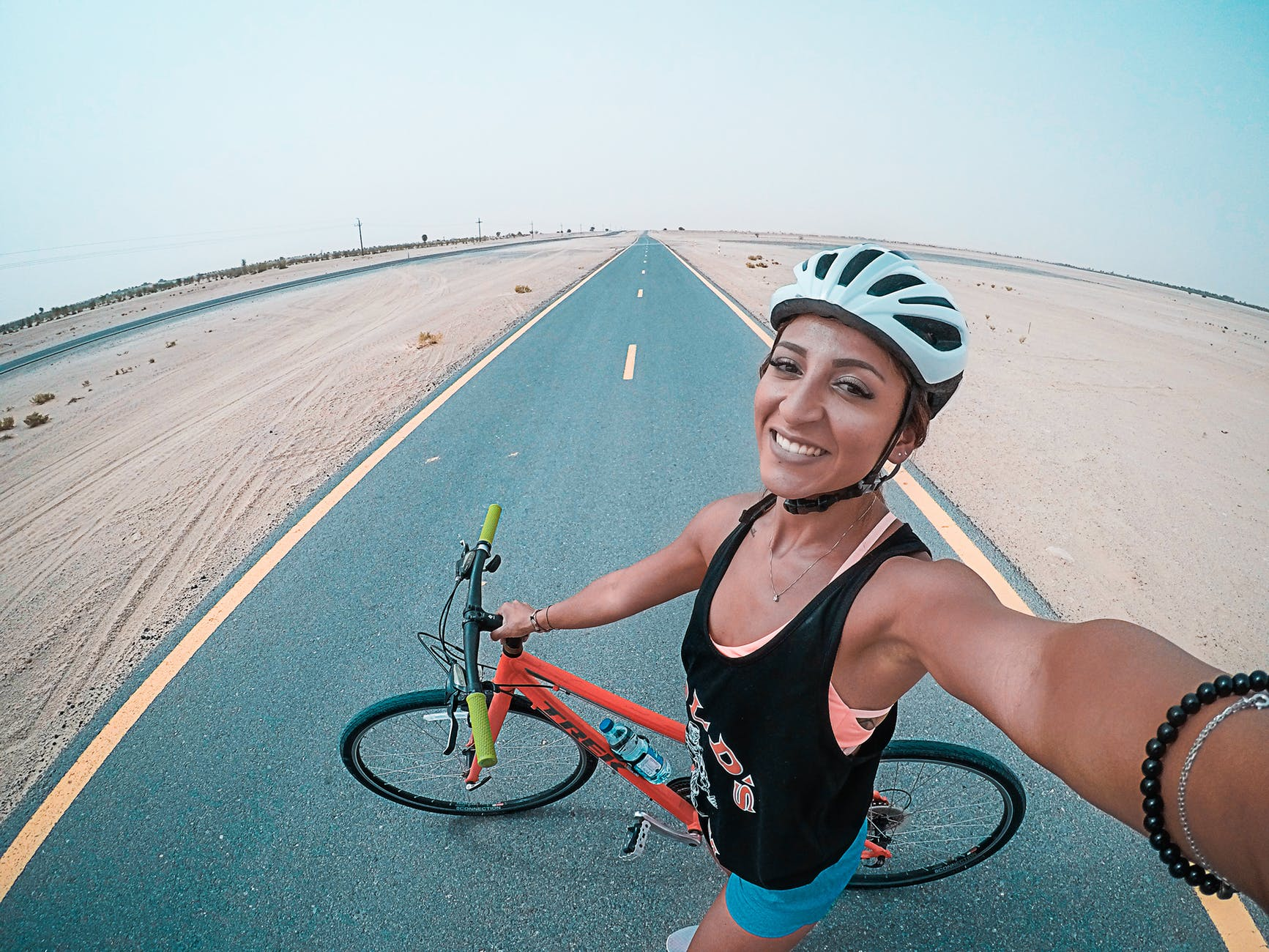 woman holding bicycle on asphalt road